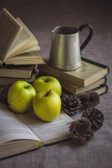Bodegón con manzanas y libros.
