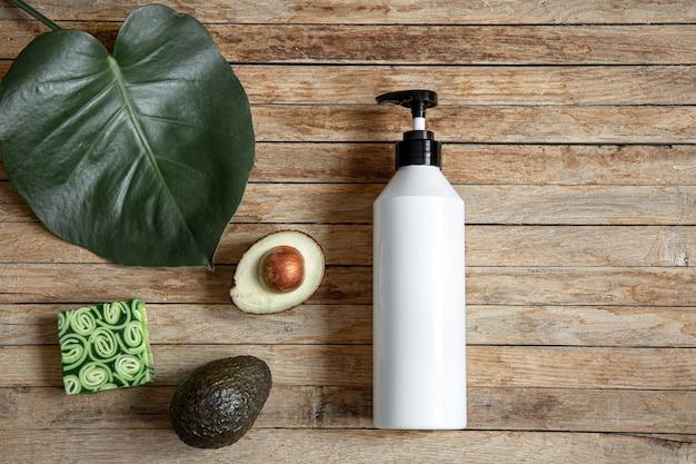 Bodegón con maqueta de botella blanca con dosificador, jabón natural y aguacate. concepto de belleza y cosmética orgánica.