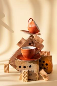Bodegón de moda con ladrillos viejos, plantas secas, taza de café y galletas en equilibrio. objetos utilizados anteriormente en espacios de vida modernos. principio de desperdicio cero