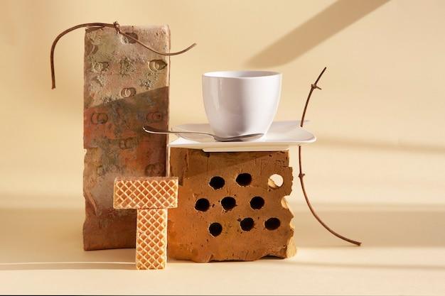 Bodegón de moda con ladrillos viejos, plantas secas, una taza de café y galletas. objetos utilizados anteriormente en espacios de vida modernos. principio de desperdicio cero