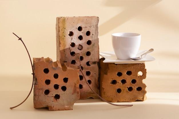 Bodegón de moda con ladrillos viejos, plantas secas y una taza de café. el uso de elementos reciclados en espacios de vida modernos. principio de desperdicio cero
