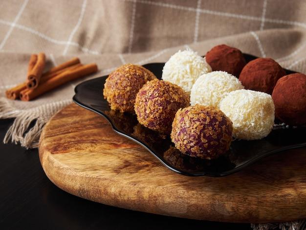 Bodegón de navidad bolas de caramelo hechas a mano en una placa negra y palitos de canela