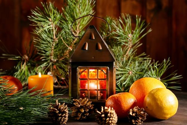 Bodegón de navidad con linterna, velas encendidas, ramas de árboles de navidad, frutas y piñas.