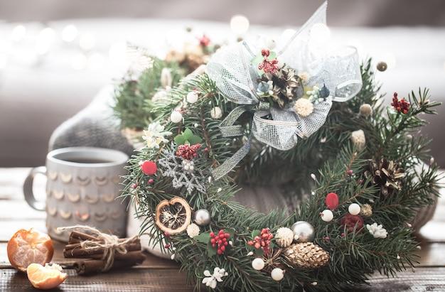 Bodegón navideño de árboles y decoraciones, guirnalda festiva sobre un fondo de ropa tejida y hermosas tazas