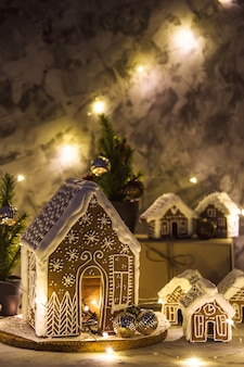 Bodegón navideño con casas de jengibre y luces de garland sobre fondo gris