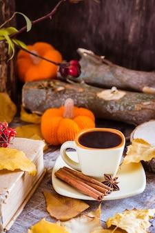 Bodegón otoñal con bebida de café. una taza de café negro y canela en un corte de un árbol.