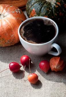 Bodegón otoñal con café, calabaza, physalis y pequeñas manzanas rojas