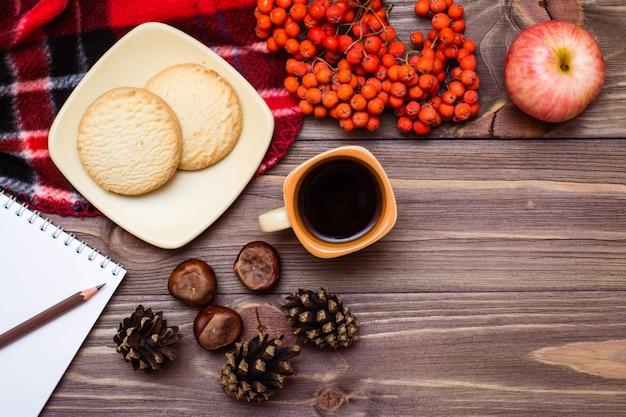 Bodegón otoñal: café, galletas, una tela escocesa, un cuaderno y un lápiz sobre madera