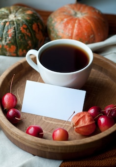 Bodegón otoñal con café, nota, calabaza, physalis y pequeñas manzanas rojas