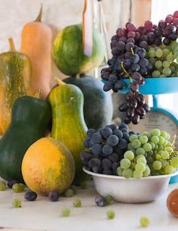 Bodegón otoñal con calabazas, melones, sandía, uvas en una escala y en un recipiente de metal sobre una mesa de madera blanca. concepto de cosecha de otoño.