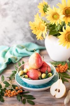 Bodegón otoñal con peras y flores de girasol sobre superficie de madera