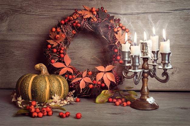 Bodegón de otoño con calabaza, corona de bayas y velas.