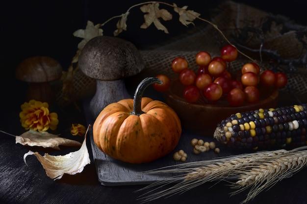 Bodegón de otoño en clave baja con calabaza naranja pequeña y decoraciones de otoño