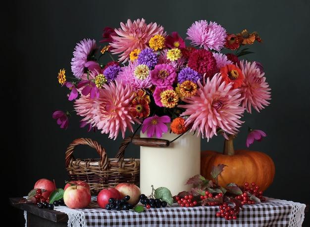 Bodegón de otoño con flores de jardín, calabaza, manzanas y bayas.