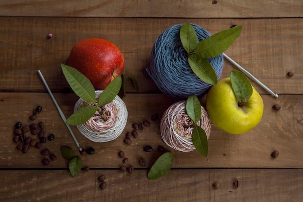Bodegón de ovillos de lana, agujas de tejer y fruta.