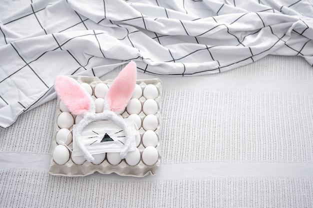 Bodegón de pascua con una bandeja de huevos, orejas de conejo de pascua decorativas y una máscara pintada. concepto de vacaciones de semana santa en el contexto de la pandemia.