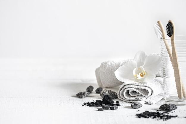 Bodegón con pinceles de bambú orgánico y polvo de carbón activado y una flor de orquídea como elemento decorativo. higiene bucal y cuidado dental.