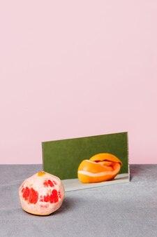 Bodegón de un pomelo pelado con su cáscara reflejada en un espejo sobre un mantel gris y rosa
