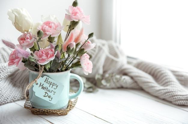 Bodegón de primavera con flores en un jarrón y la inscripción feliz día de la madre en la postal.