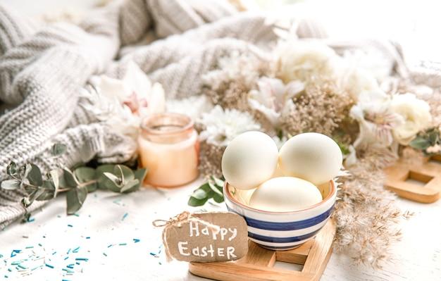 Bodegón de primavera con huevos de pascua en un hermoso platillo contra detalles decorativos. concepto de vacaciones de semana santa.