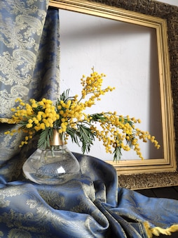 Bodegón de primavera con mimosa en un jarrón y un marco dorado viejo con una cortina de tela