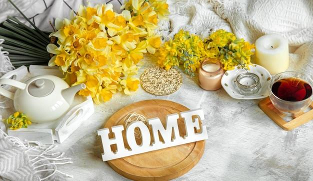 Bodegón de primavera con una taza de té y flores en la mesa de luz. concepto de hogar acogedor.