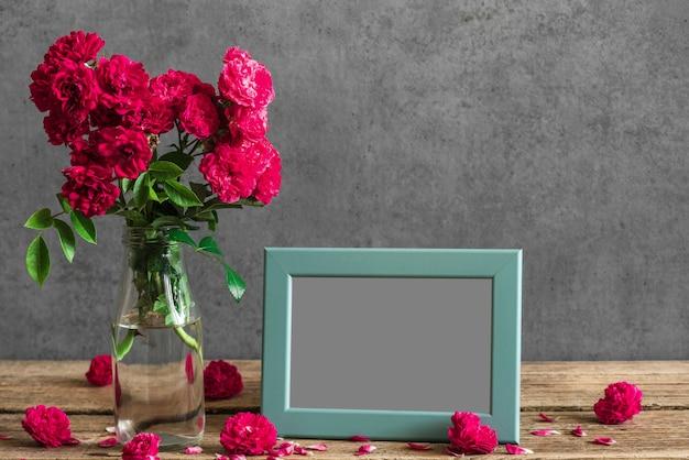Bodegón con ramo de flores rosas rojas, marco de fotos en blanco y brotes