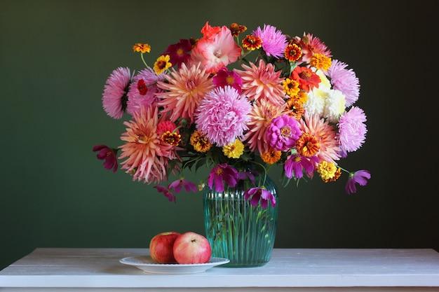 Bodegón con ramo y manzanas. asters, dalias y diferentes flores de otoño en un jarrón.