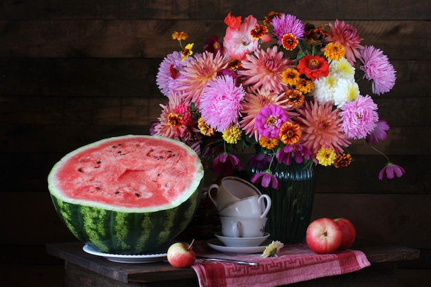Bodegón con ramo y sandía. asters, dalias y diferentes flores de otoño en un jarrón.