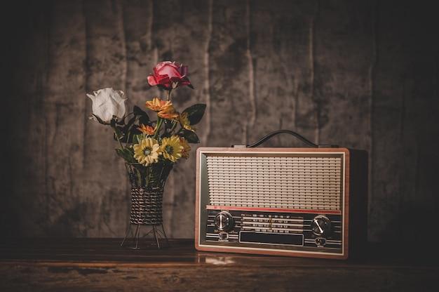 Bodegón con un receptor de radio retro y floreros