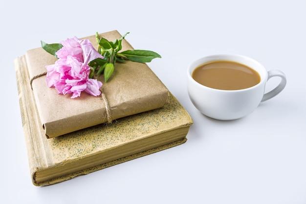 Bodegón romántico vintage con libro viejo, taza de té o café, bonita caja de regalo envuelta con papel artesanal y decorada con flor rosa sobre fondo blanco.