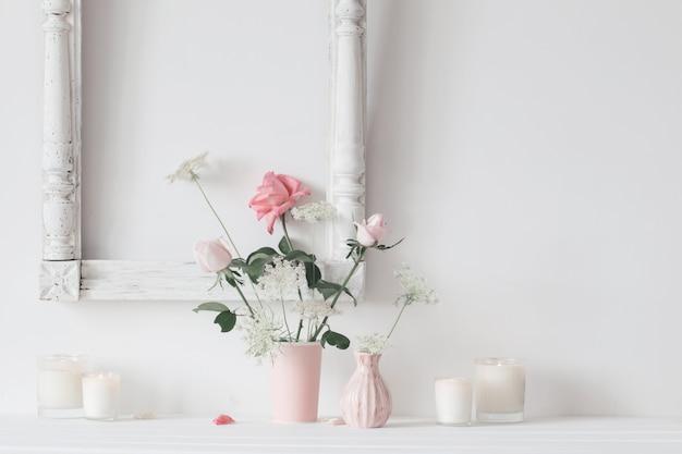 Bodegón con rosas rosas y velas sobre fondo blanco.