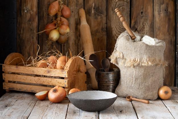 Bodegón rústico, harina, cebolla, huevos y especias en una mesa de madera.