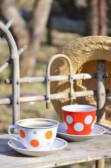 Bodegón rústico con tazas de té y sombrero de paja.