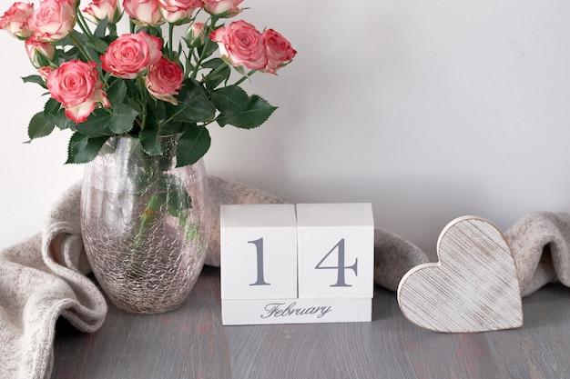 Bodegón de san valentín con calendario de madera, corazón rústico, bufanda y rosas rosadas