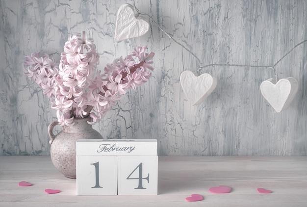 Bodegón de san valentín con calendario de madera, flores de jacinto rosa y luces de guirnaldas en forma de corazones