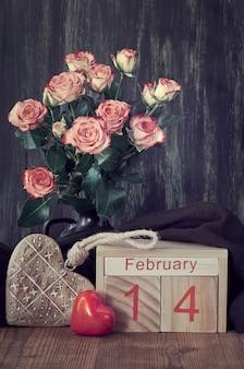 Bodegón de san valentín con calendario de madera, rosas rosadas y corazones en la oscuridad