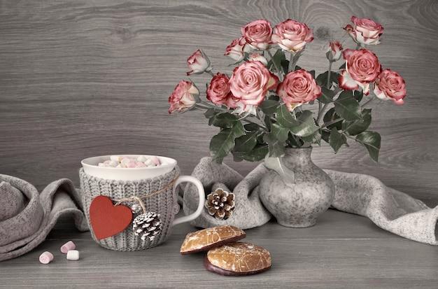 Bodegón de san valentín con una taza de chocolate caliente con malvaviscos, rosas rosadas y bufanda