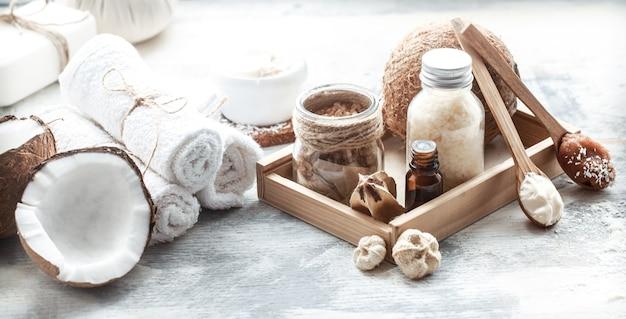 Bodegón de spa con coco fresco y productos para el cuidado corporal