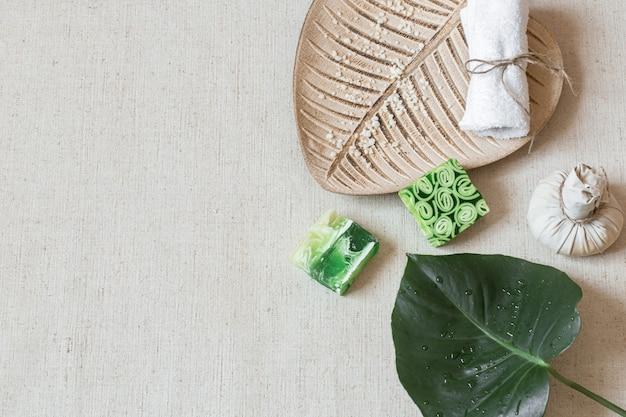 Bodegón de spa con jabón, toalla, hojas y vista superior de sal marina. concepto de higiene y belleza.
