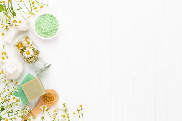 Bodegón de spa con manzanilla de aromaterapia, aceite de hierbas, jabón, sal marina.