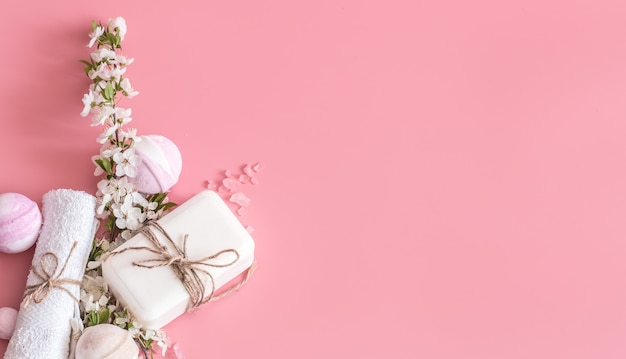 Bodegón de spa en pared rosa con flores de primavera