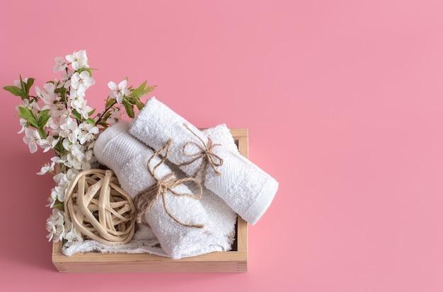 Bodegón de spa sobre fondo rosa con flores de primavera