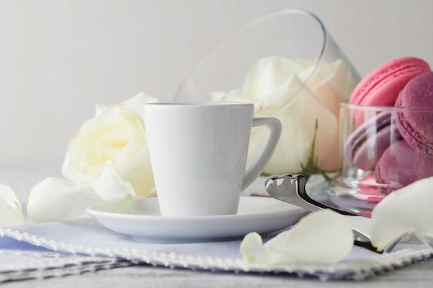 Bodegón con taza de café y flores.