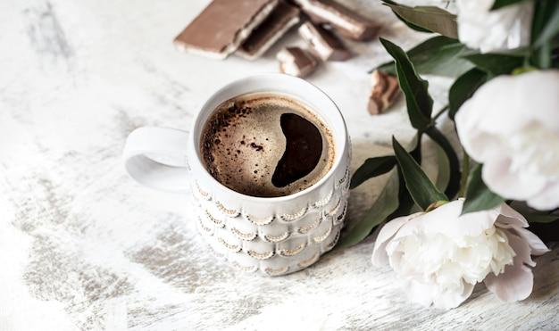 Bodegón con una taza de café y flores.