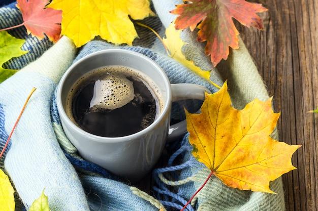 Bodegón una taza de café y hojas de otoño con cuadros