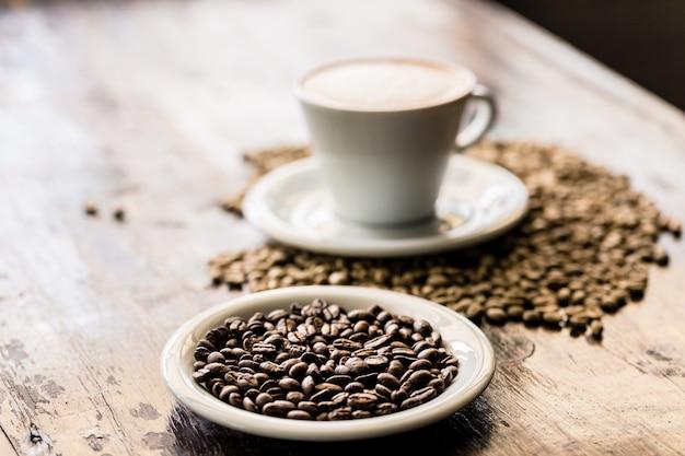 Bodegón de taza de capuchino y granos de café.