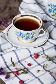 Bodegón con taza de té y mantel en mesa de madera