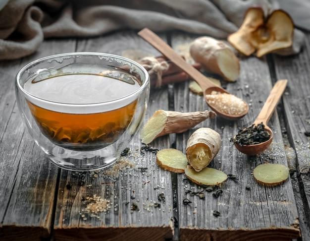 Bodegón con taza de té transparente y fragante con jengibre sobre fondo de madera