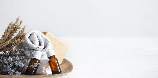 Bodegón con toallas, jabón y aceites aromáticos en tarros.